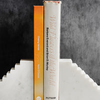 2: A pair of white marble bookends with staircase design, shown with two books.