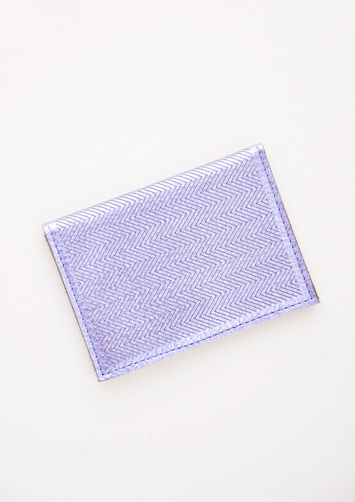 Metallic Periwinkle: Slim metallic blue leather wallet with two interior slip pockets that folds closed with a snap, shown closed with zig zag etched pattern.