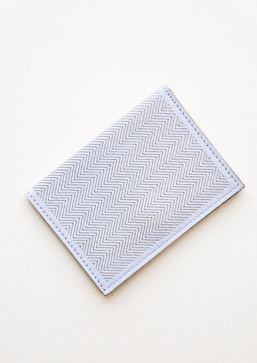Dusty Blue: Slim light blue leather wallet with two interior slip pockets that folds closed with a snap, shown closed with zig zag etched pattern.