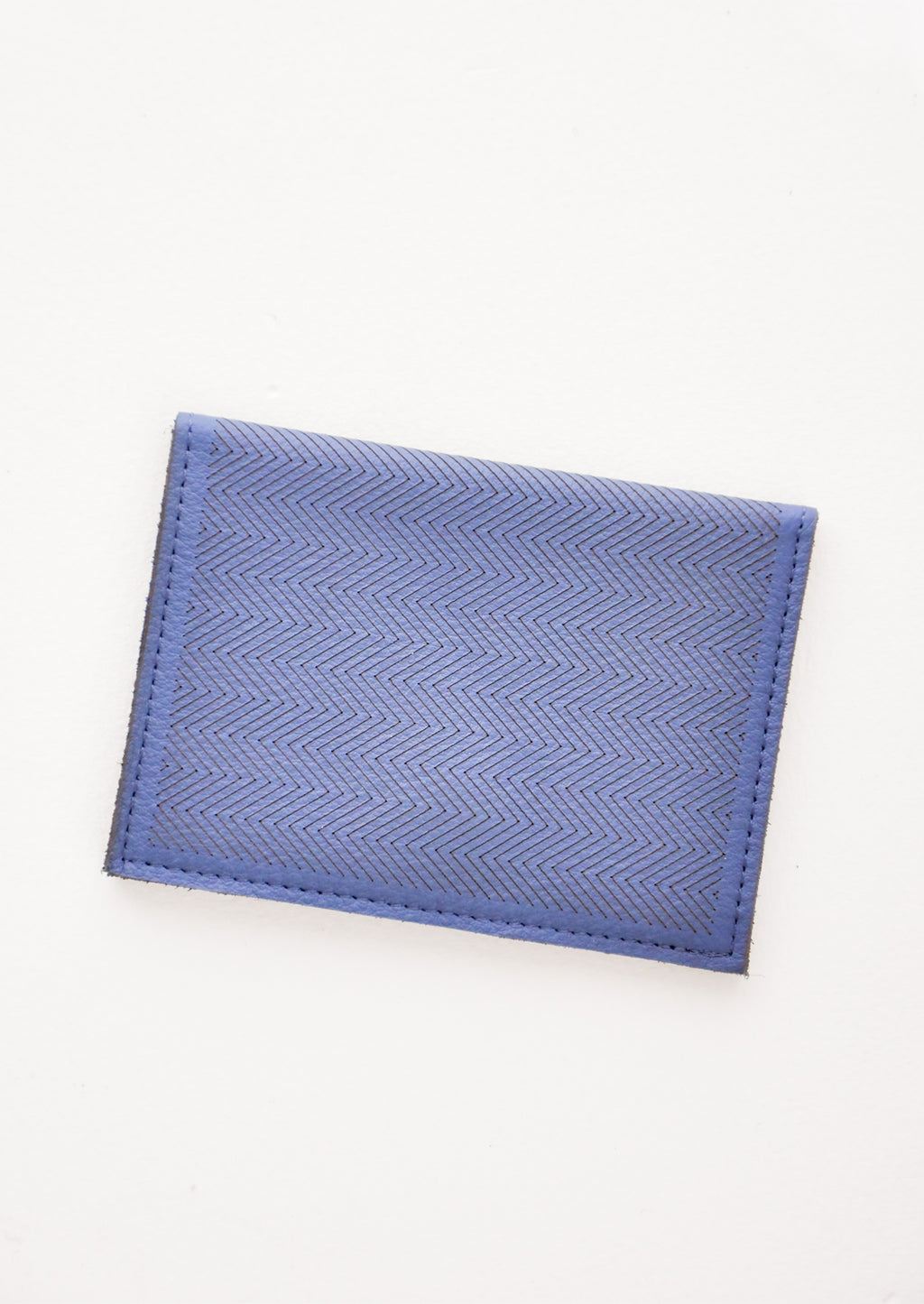 Indigo Blue: Slim dark blue leather wallet with two interior slip pockets that folds closed with a snap, shown closed with zig zag etched pattern.