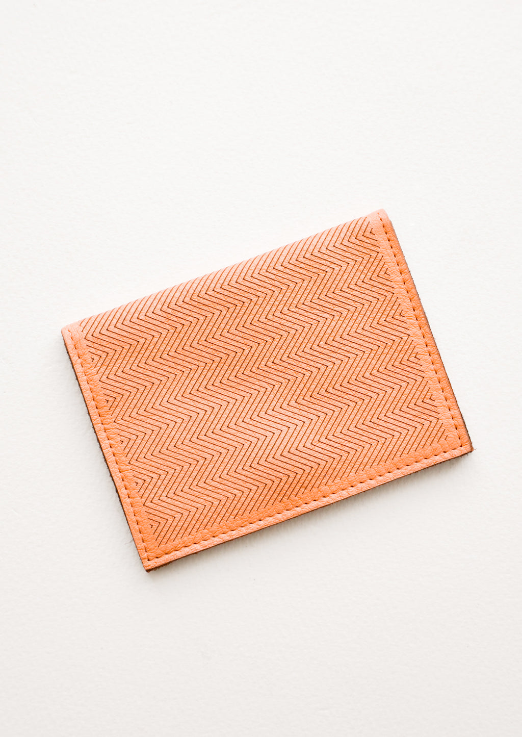 Terracotta: Slim terracotta orange leather wallet with two interior slip pockets that folds closed with a snap, shown closed with zig zag etched pattern.