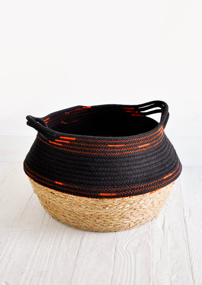 Round, low storage basket with woven straw bottom half and dark fabric top half featuring neon orange stitching