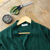 green bamboo silk robe on hanger with pins and scissors
