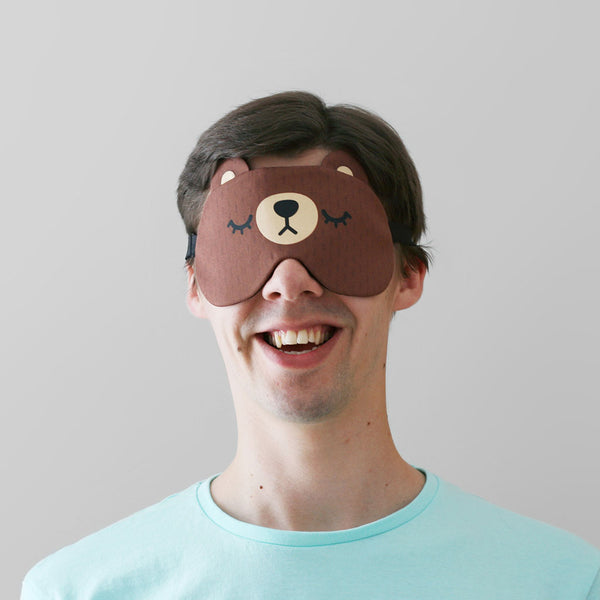 Man modelling brown bear sleep mask