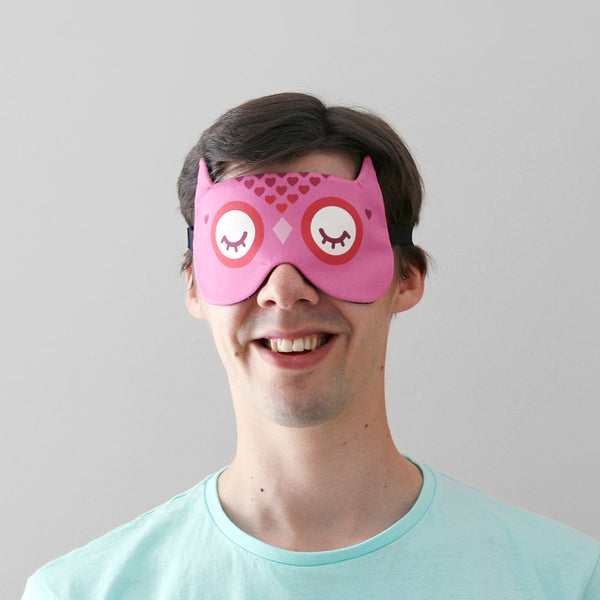 Man wearing owl sleep mask with heart pattern