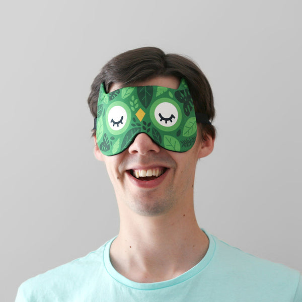 Man wearing owl sleep mask with green leaves