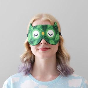 Woman wearing green leafy owl mask