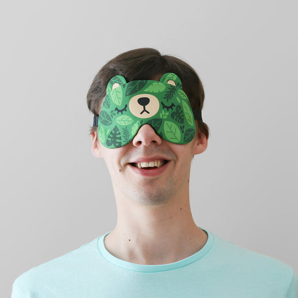 A man wearing a bear sleep mask with a green leaves pattern