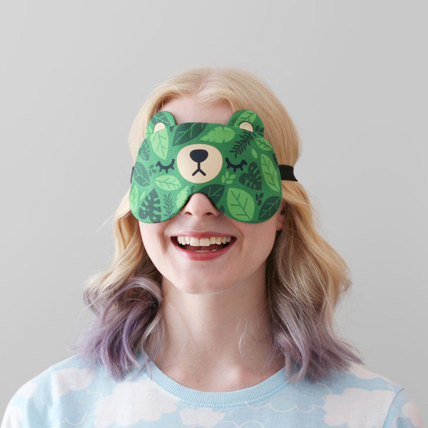 A woman wearing a bear sleep mask with a green leaves pattern