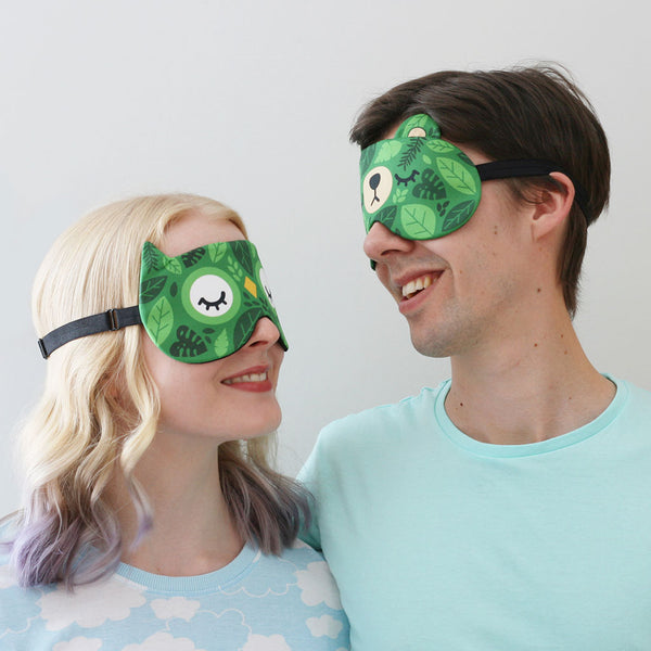 Couple wearing sleep masks with leafy green patterns