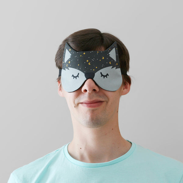Man wearing fox sleep mask with starry night pattern