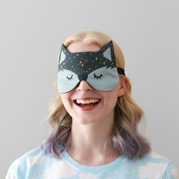 Woman wearing sleep mask with starry night pattern