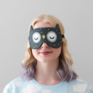 Woman wearing owl sleep mask with starry sky pattern