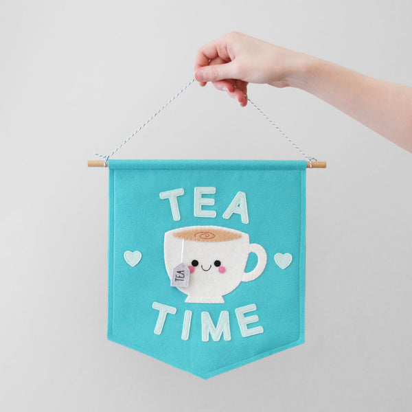 Hand holding blue felt banner with a teacup and 'TEA TIME' felt details
