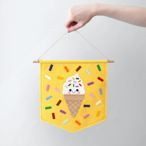 hand holding a yellow felt flag wall banner with a swirly ice cream