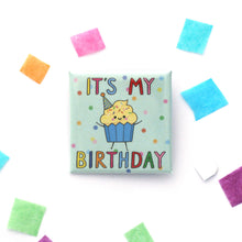 An illustrated square button badge with a happy vanilla cupcake wearing a birthday hat and 'IT'S MY BIRTHDAY' text
