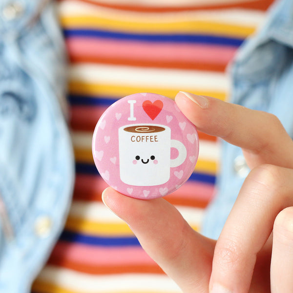 Person holding coffee button badge