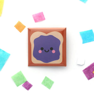 A happy sandwich badge with a spread of purple jelly