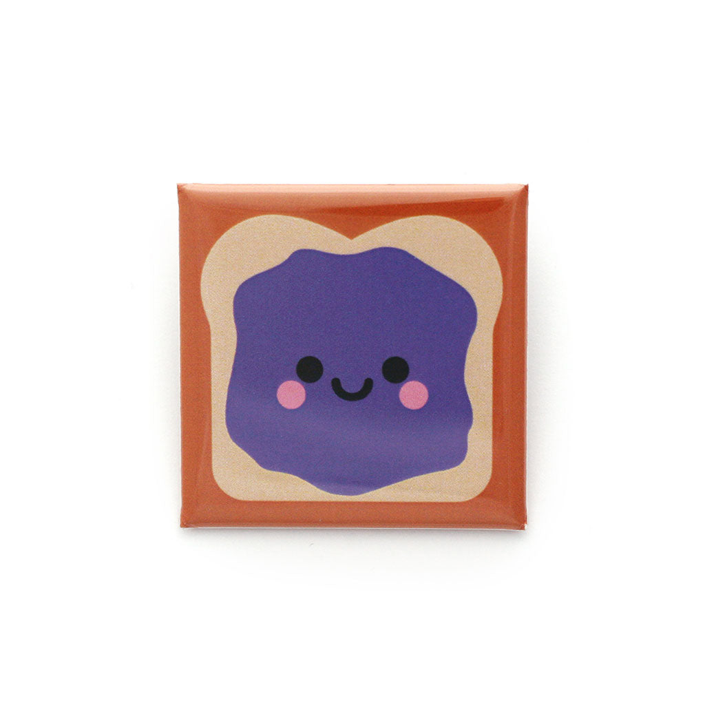 A 38mm square sandwich badge with a smear of purple jelly and a smiley face