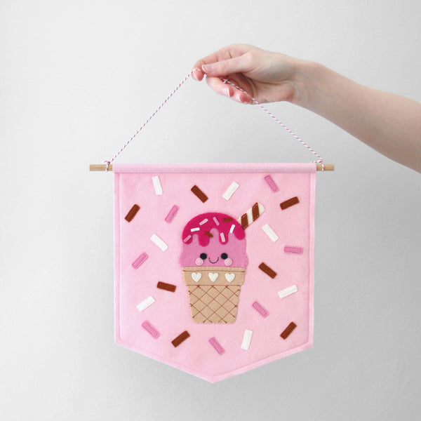 hand holding a pink wall banner with an ice cream and sprinkles decorating it