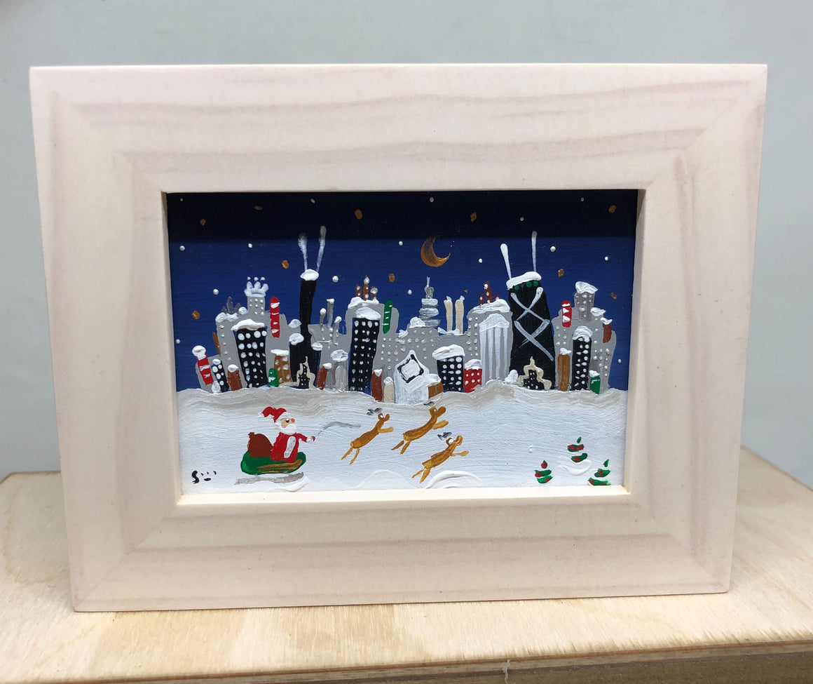 miniature painting of santa in his sleigh with the Chicago skyline.  it is night the snow covers the buildings.  Hand painted by artist Joe Smigielski
