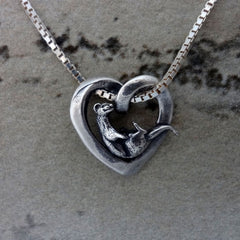 Otter in a heart pendant