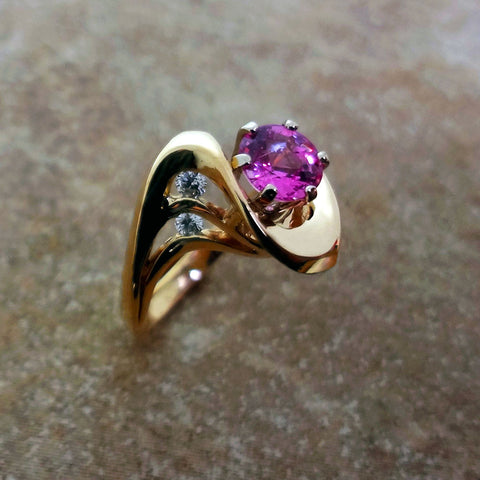 Very feminine ribbon of 14kt yellow gold graces a 1.01ct  pink Sapphire with .12 tcw Diamond accents.