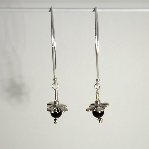 "Sterling silver handmade limited edition earring 2-1/2 inches long.  The wire wrapped dangle is a four petaled flower, sterling beads and a 6mm genuine black onyx bead dangle.  Pretty and modern big ""V"" shepherd hook. Custom made by All Animal Jewelry and Jan David Design Jewelers."