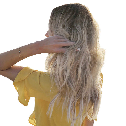 woman from behind running fingers through long wavy hair