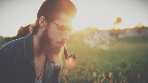 A man with glasses and a beard smoking a pipe