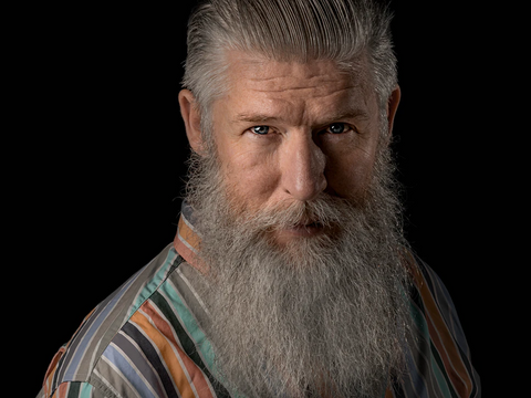 An older bearded man looking at the camera
