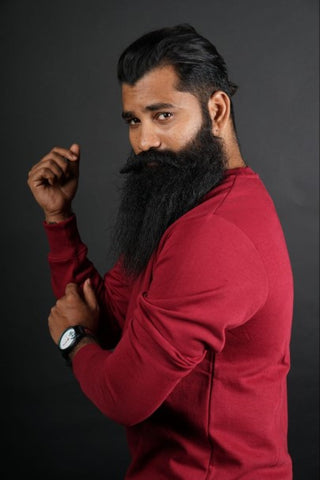 Man with long beard and red shirt rolling up his sleeve