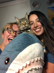 Photo of Jaclyn and Yasmin and their cat holding a plush shark