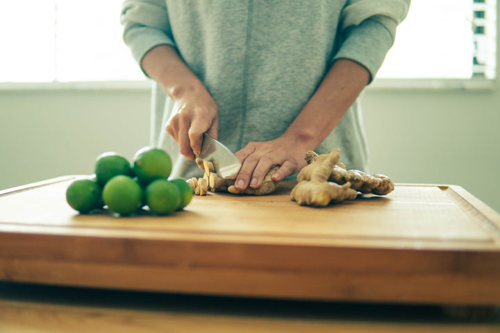 Woman chopping fresh ginger, next to a pile of limes on a wooden cutting board