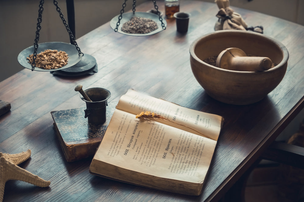 Apothecary inspired table with book, mortar and pestle, and natural elements.