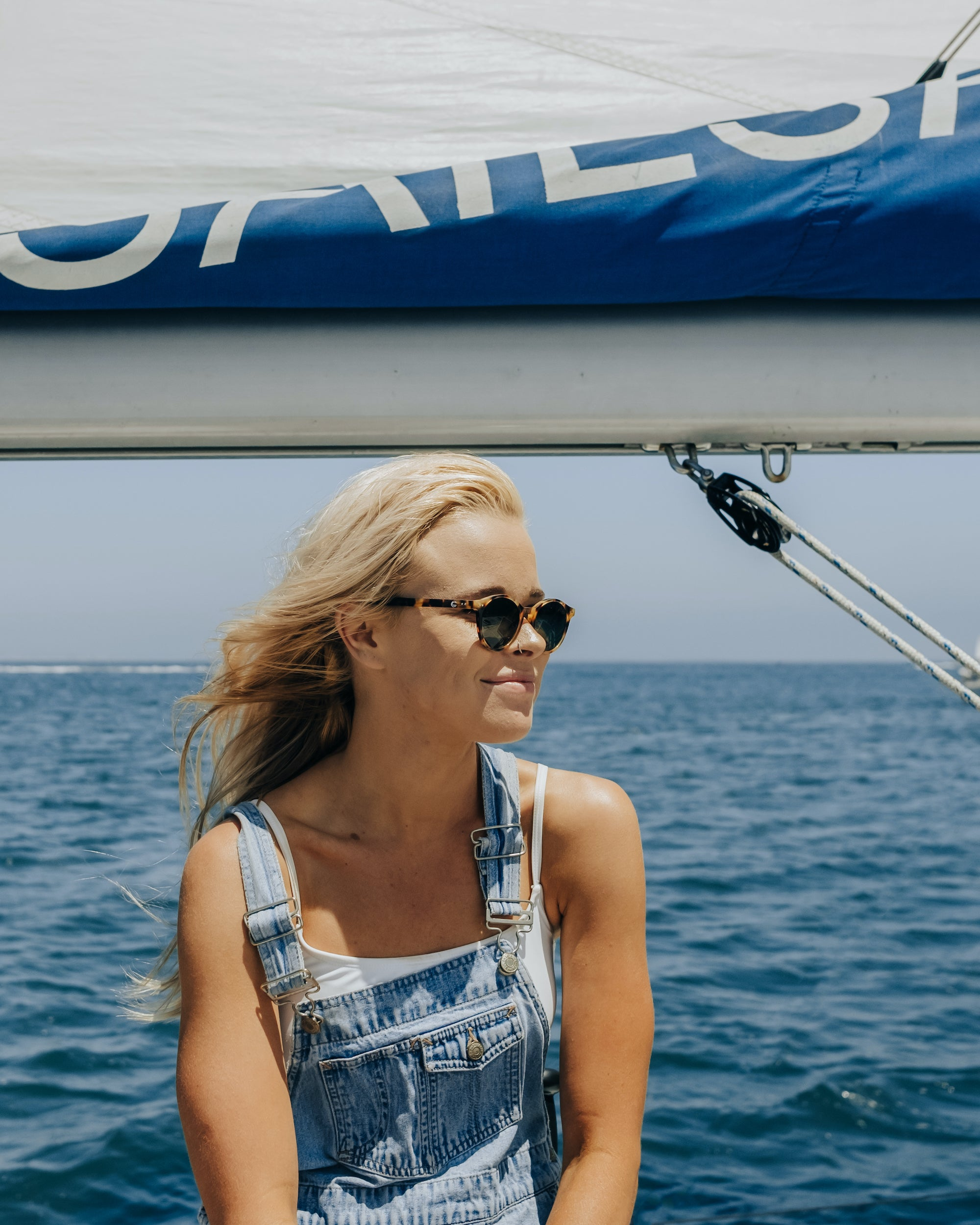 girl on sailboat wearing sala verde oceansafe sunglasses