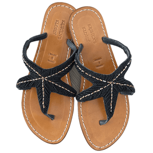 Handmade Leather Beaded Sandals are shown in Black. Leather uppers and soles all made by hand. Beading is delicate black beads interlocked with gold beading to form a Starfish Design.