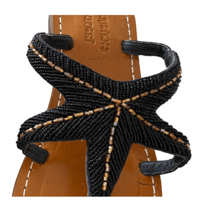 Handmade Leather Beaded Sandals are shown in Black. Leather Uppers and soles all made by hand. Beading is delicate black beads interlocked with gold beading to form a Starfish Design. Close up view of beading.