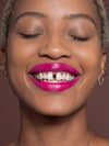 Woman wearing magenta lipstick and smiling