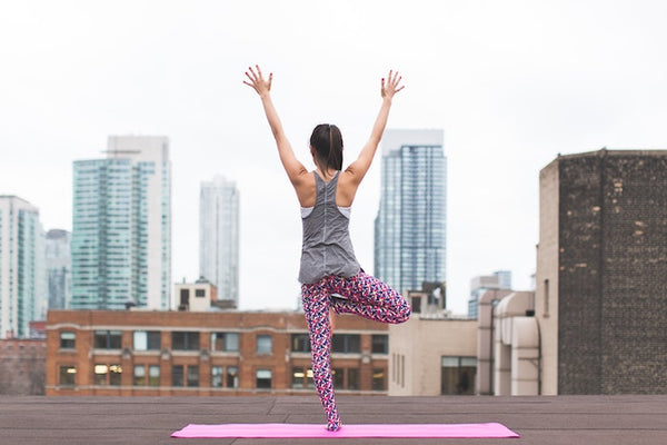Woman doing yoga on a city rooftop