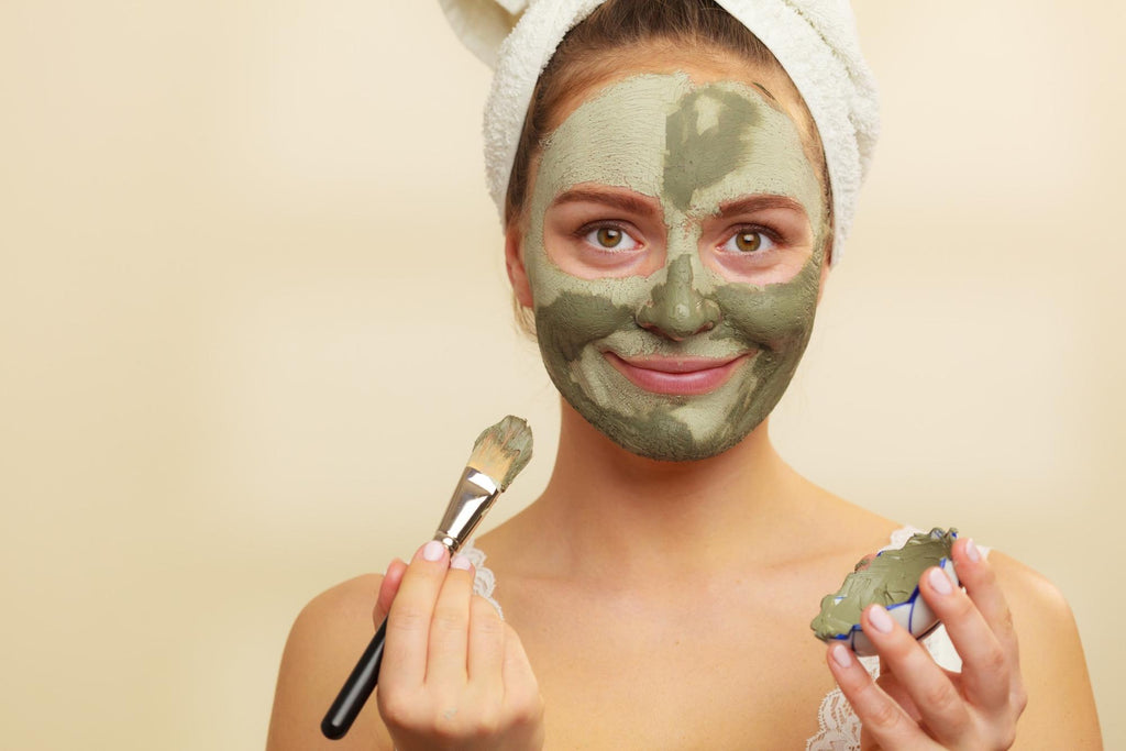 Woman puts French green clay mask on with a towel on her head