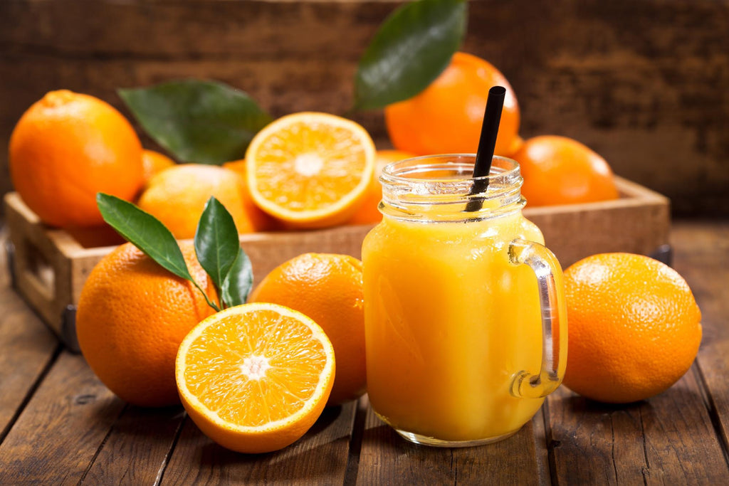Remineralize teeth: Glass of orange juice next to many oranges