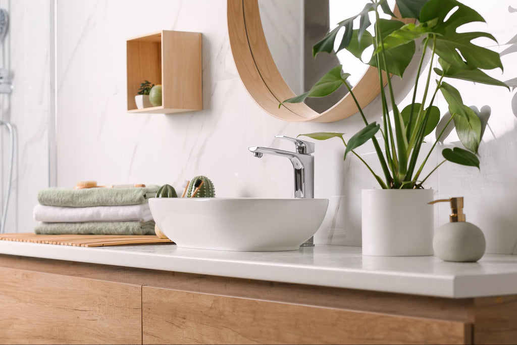 Bathroom sink with folded towels and plants