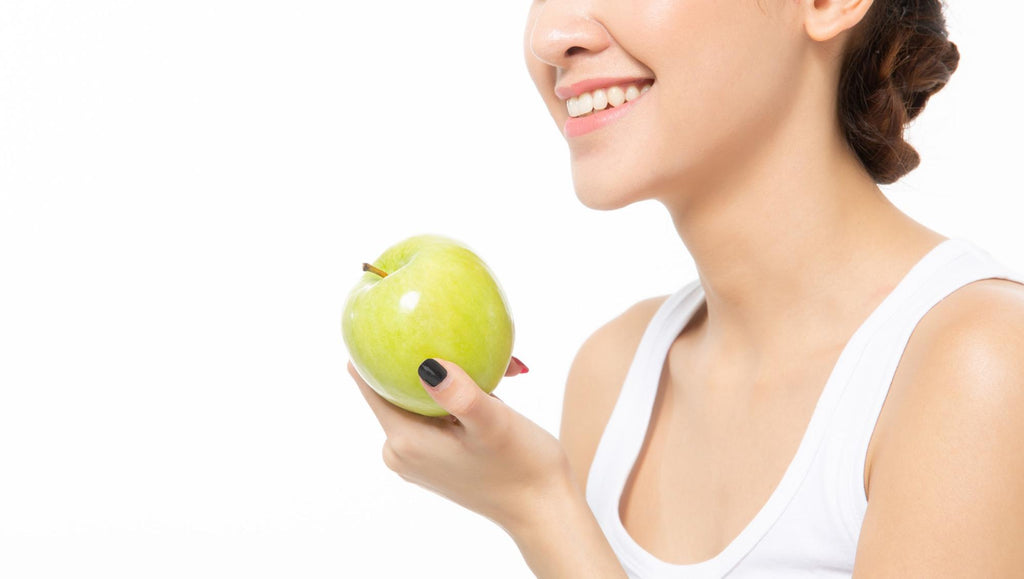 Remineralize teeth: Woman holds apple