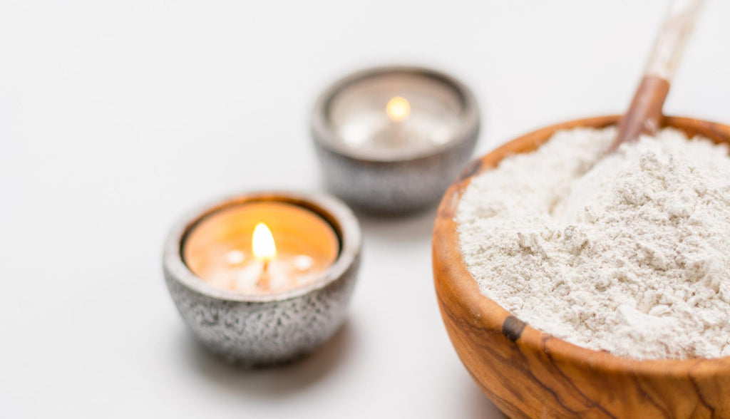 Bowl of powdered kaolin clay with lit candles