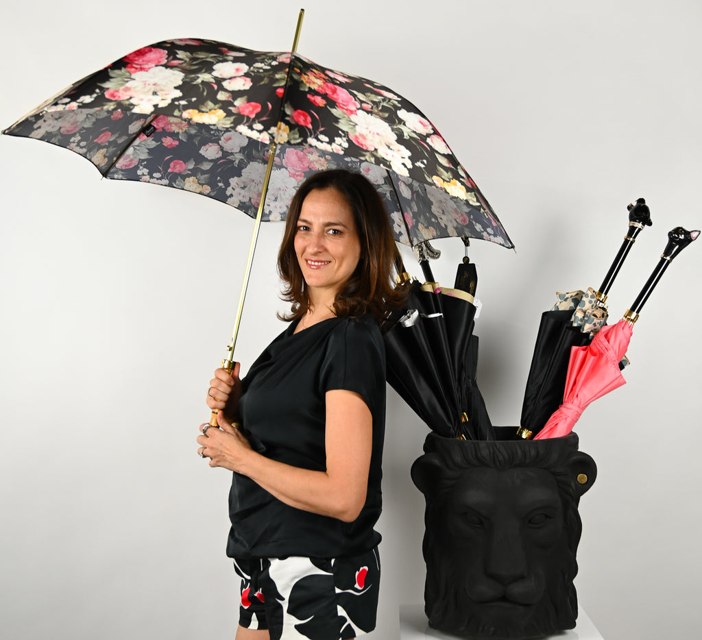Woman holding Pasotti black flower parasol beside Garden glory lion pot as umbrella stand with pasotti umbrellas