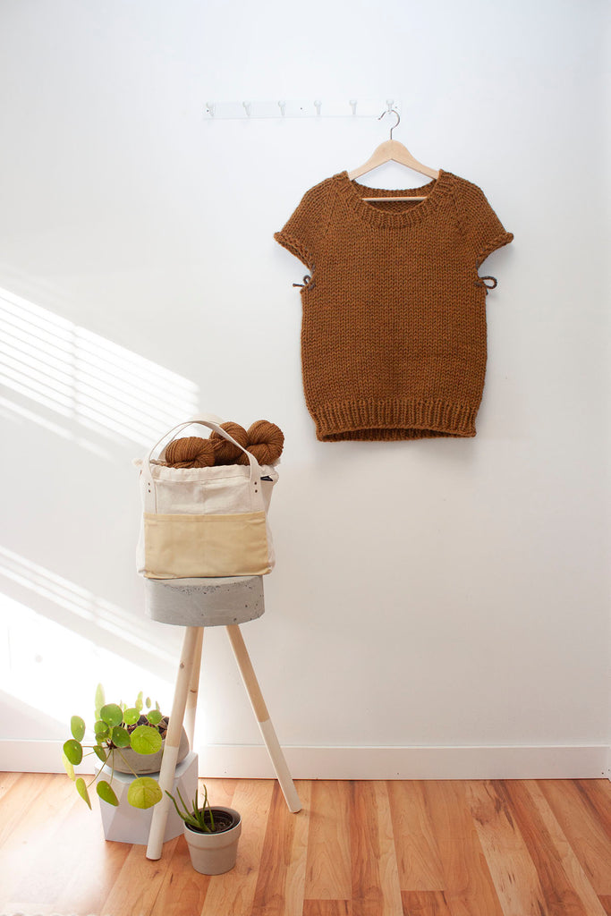 a half finished handknit sweater hangs on a hanger against a white wall
