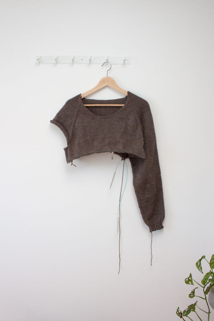 a half finished men's raglan sweater in brown hangs from a hanger against a white wall