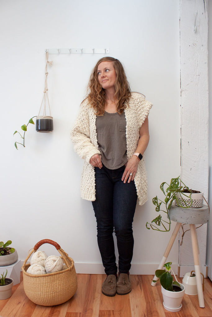 woman wearing an unfinished oversized textured handknit cardigan in a cream colour standing against a white wall