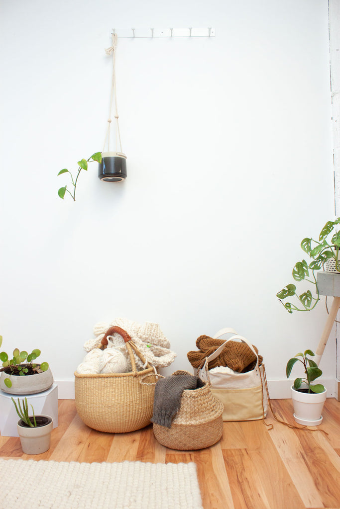 multiple knitting projects in bags and baskets on the floor surrounded by house plants